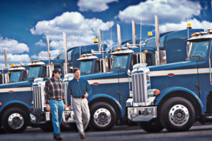 2 Men Walking with Semi Trucks in Background